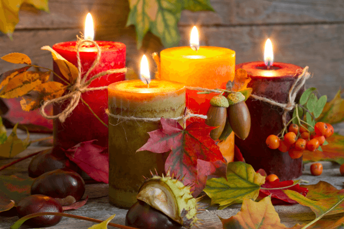 autumn candles with maple leaves and chestnuts