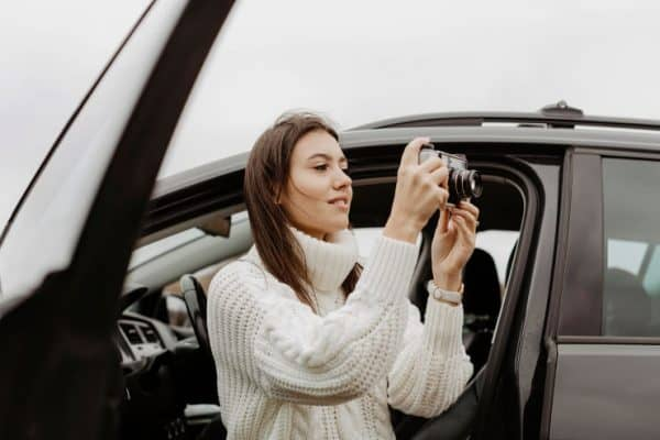 girl getting out of car and taking a photo