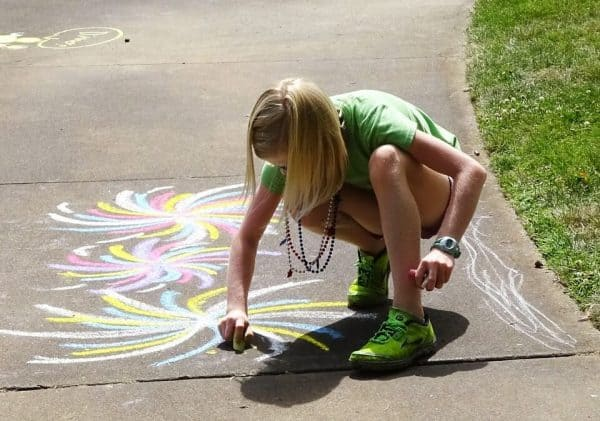 Girl creating chalk art on sidewalk- pixabay
